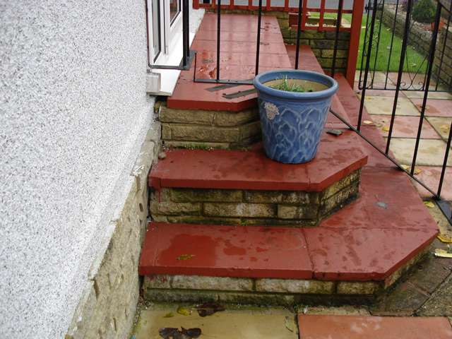 A photo of 3 outside steps leading to an entry door of a domestic property. A Powerstep step lift offers a great solution for users to get up and down steps like these.