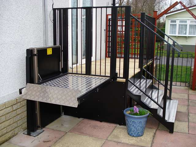A photo of a Powerstep steplift solution installed to allow users to get up and down the steps shown in this photo gallery: images 4, 5, and 6. The wheelchair lift is shown in the raised position level with the top step.