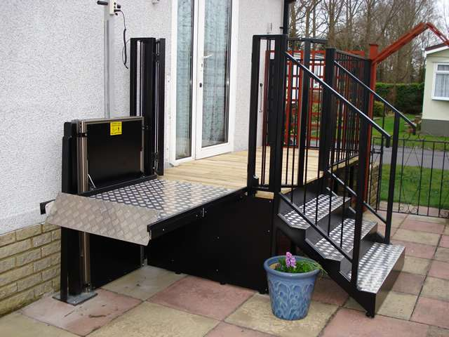 A photo of a Powerstep steplift solution installed to allow users to get up and down the steps shown in this photo gallery: images 4, 5, and 6. The wheelchair lift is shown in the raised position level with the top step, with the wheelchair access gates now open.