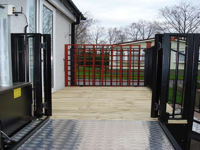 Looking directly through the wheelchair lift in the raised position, with wheelchair access gates open, a photo of a Powerstep steplift solution installed to allow users to get up and down the steps shown in this photo gallery: images 4, 5, and 6.