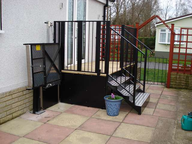 A photo of a Powerstep steplift solution installed to allow users to get up and down the steps shown in this photo gallery: images 4, 5, and 6. The wheelchair lift is shown in the down position, with the wheelchair platform folded back vertical to the property wall, to provide minimal obstruction to other users when not in use or required by mobility users.